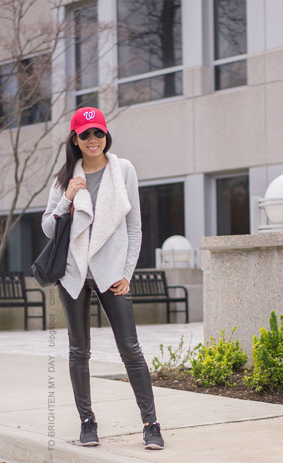 red cap, sherpa-lined cozy open cardigan, gray tee, black faux leather pants, black sneakers