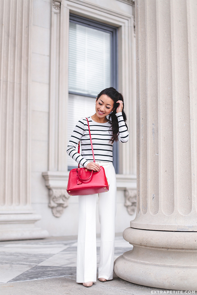 white pants striped tee work outfit red prada bag