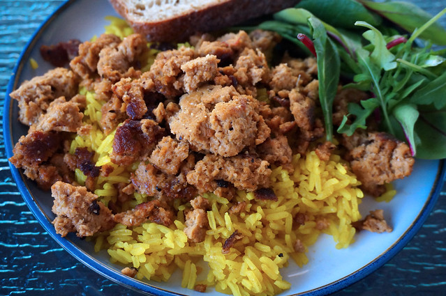 A plate of street-cart seitan and yellow rice, not yet sauced. Salad and bread occupy the border of the plate