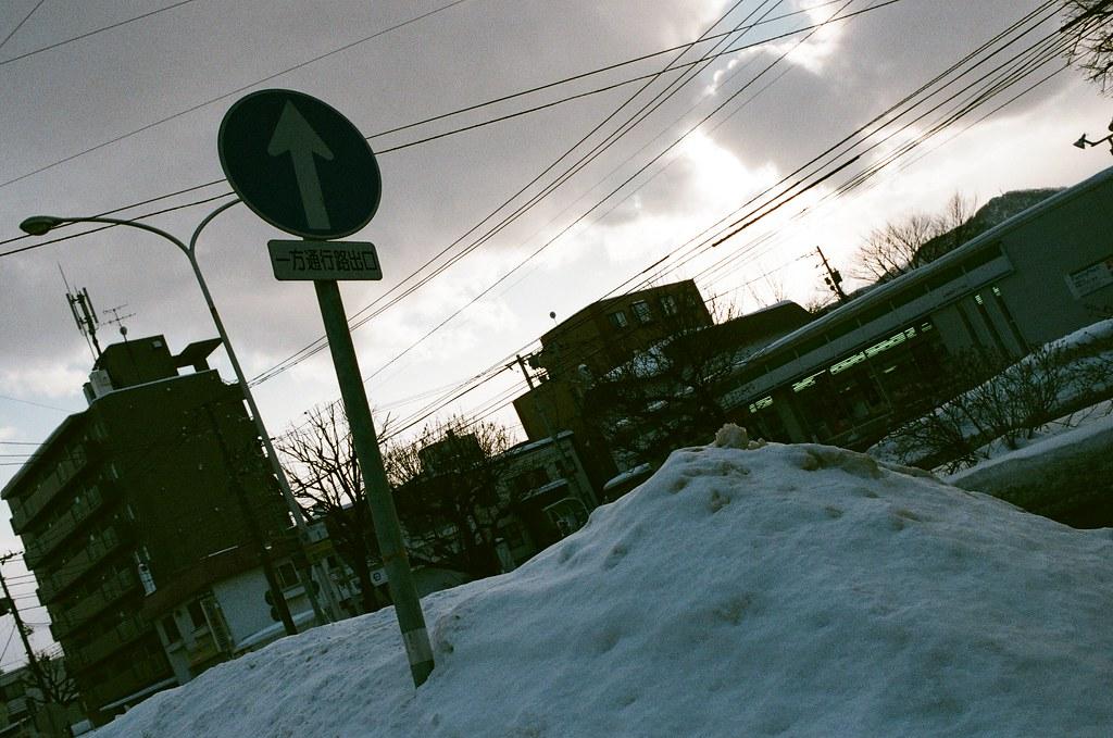 學園前 札幌 北海道 Sapporo, Japan / AGFA VISTAPlus / Nikon FM2 2016/01/31 住的地方在學園前站(gakuenmae),把行李安置好後在附近走走,但那時候南北方向搞錯了,本來想要走回大通公園,結果越走越南,之好走到下一站平岸往回搭。  一路上就隨意走走拍拍,一直觀察路上的積雪,沒有看過,所以很好奇。雪自然的堆疊起來後的表面很光滑,輕輕一碰就凹陷下去。  那時候拍到一半相機沒電,在寒冷的情況下,手不聽使喚的完成換電池的挑戰!  Nikon FM2 Nikon AI AF Nikkor 35mm F/2D AGFA VISTAPlus ISO400 8264-0030 Photo by Toomore