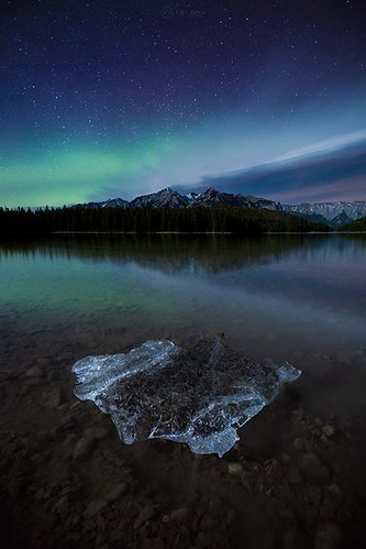 """Fragment of Winter"" A piece of ice lies stranded on the shore of Two Jack Lake, its final resting place. In the background, a fleeting aurora contrasts with mountains that have been around for millions of years. Banff National Park, Canada. -------------"