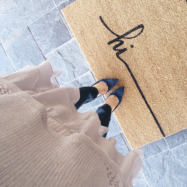 cute & little blog | petite fashion | lo rustique doormat | peplum gray sweater, rag bone jeans, navy suede pumps | front door home decor
