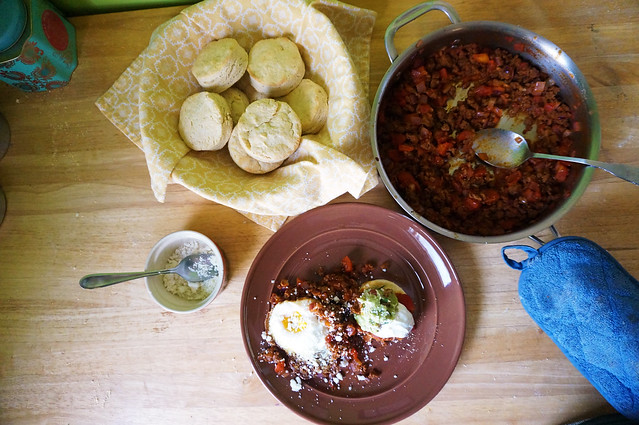 Seen from above, a wooden counter laid with a a skillet full of reddish brown chorizo topping, a ramekin of crumbly cotija cheese, a bowl of biscuits lined with a bright yellow napkin, and a plateful of biscuits and chorizo, topped with a fried egg, guacamole, and sour cream. I could dive right into this counterscape.