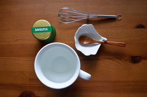 Matcha Supplies: A cup of nearly boiling hot water, spoon, whisk, and matcha