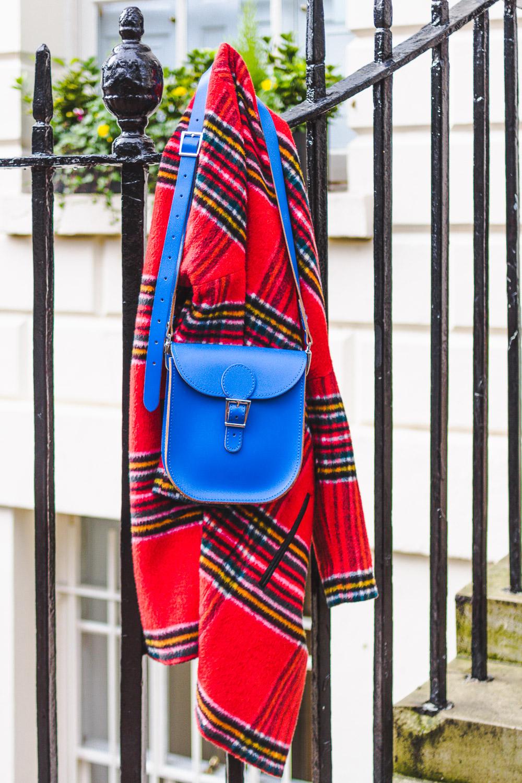 red coat blue bag hung up on railings
