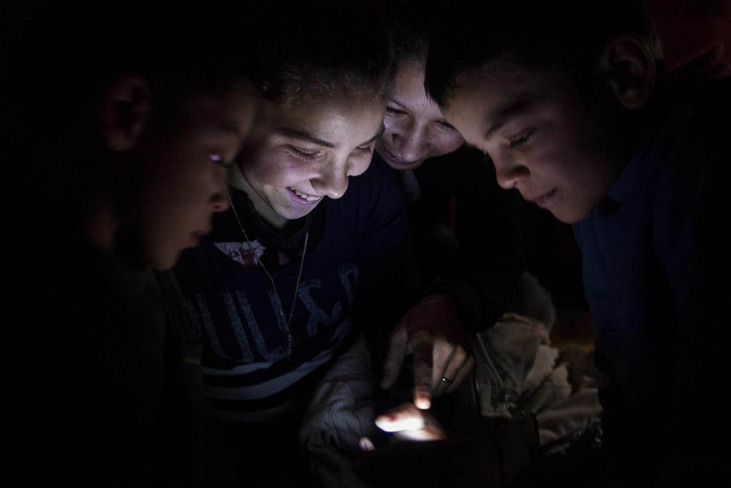Terike három gyereke és egy barátnőjük az egyikük mobiltelefonján néz valamit. Az áramot a hátralék miatt kapcsolták ki. Terike szerint ez eredetileg körülbelül negyvenezer forint volt, ami aztán nyolcvanezresre duzzadt a kamatokkal, de ezt aztán segítséggel rendezték. Csakhogy közben hozzá jött még egy 160 ezres végrehajtási költség is. A villanyóra szerinte hatvanezer forintnál is magasabb visszaszerelés költségével együtt ez már olyan összeg, amit nem tudnak előteremteni. Egy kistévé árválkodik a sarokban, de bekapcsolva rég volt, a mobiltelefonokat ismerősöknél töltik, szívességi alapon. | Fotó: Magócsi Márton