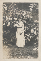 Woman posing among her tall flowers