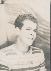 Photo booth portrait of a young man in front of an American flag background 1