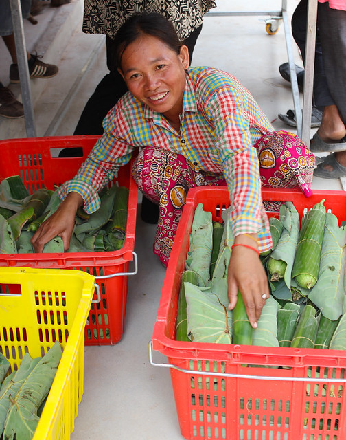 Woman kneeling, sorting sponge gourds individually wrapped in banana leaves into different crates IMG_4636-eds-blog