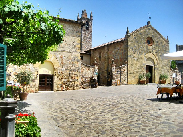 Main square of Monteriggioni, with the facade of the church and the small fountain