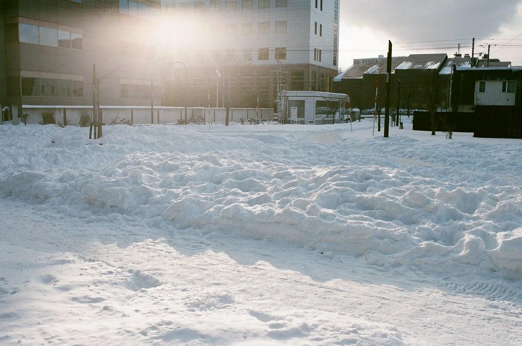 學園前 札幌 北海道 Sapporo, Japan / AGFA VISTAPlus / Nikon FM2 2016/01/31 住的地方在學園前站(gakuenmae),把行李安置好後在附近走走,但那時候南北方向搞錯了,本來想要走回大通公園,結果越走越南,之好走到下一站平岸往回搭。  一路上就隨意走走拍拍,一直觀察路上的積雪,沒有看過,所以很好奇。雪自然的堆疊起來後的表面很光滑,輕輕一碰就凹陷下去。  那時候拍到一半相機沒電,在寒冷的情況下,手不聽使喚的完成換電池的挑戰!  Nikon FM2 Nikon AI AF Nikkor 35mm F/2D AGFA VISTAPlus ISO400 8264-0024 Photo by Toomore