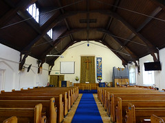 A view along the aisle of a church, with pews to either side.  A blue carpet runs along the aisle.  The pipe organ from the previous photo is in the distance on the right.  The roof is arched and has a couple of skylights.