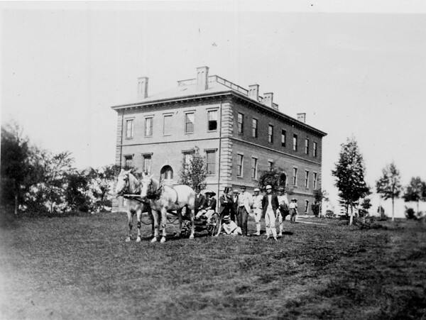 """Ballou Hall, mowing the campus with a horse and carriage, ca 1890"". 1890. Tufts University. Digital Collections and Archives. Medford, MA."