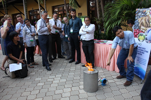 Man points to a compact stove with flame, while group looks on, with ECHO banner and information table in background IMG_7499