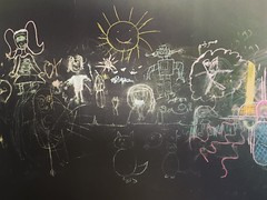 Black board with children's doodle at the international book fair ..somethings never change .. Why does the sun have spiky rays? #insta_bahrain #children_drawing #art #igr_bah_ #ig_bahrain_ #igr_bahraini