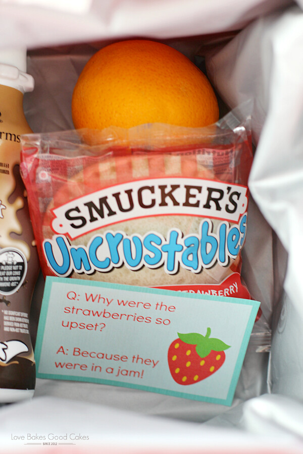 Inside of lunch box including Smuckers Uncrustables, an orange, and a bottle of chocolate milk.