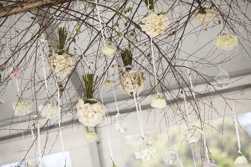 Flowers and glass hung from ceiling - wedding decoration for an outdoor rustic wedding | Photo by Blumenthal Photography | Read this real wedding on I take you - UK wedding blog