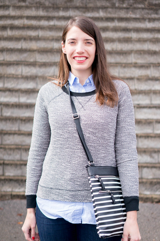 blue oxford shirt + gray sweatshirt + jeans + black and white stripe purse | Style On Target