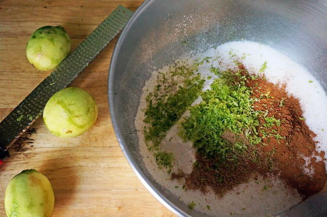 In a metal mixing bowl, flour and sugar are topped with heaps of cinnamon and coriander, the whole thing covered in a heap of tangly lime zest: heaven. Next to the bowl, 3 denuded limes and the microplane that zested them. This might be what heaven looks like.
