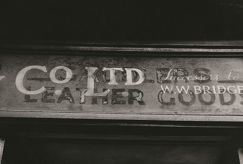 A partial view of a shop sign, '...co. ltd. Successors to W.W. Bridge..' printed over the sign 'leather goods'. 1961.