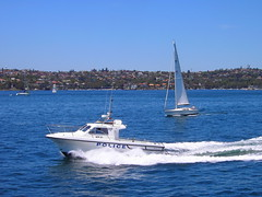 Sydney. Sailing boat and Police Boat on the harbour.