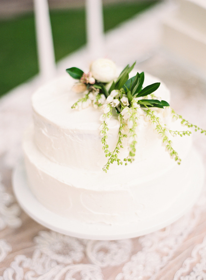 White wedding cake topped with lily of the valley