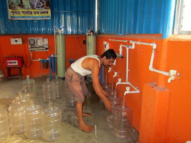 परिष्कृत पानी को जार में भरता कर्मचारी
