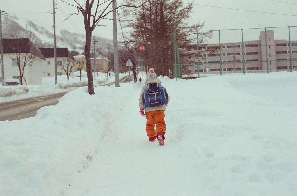 小樽 Otaru 北海道 / Fujifilm 500D 8592 / Nikon FM2 2016/02/02 從小樽運河一路走到天狗山,這段是最後的上坡,一路上一直走,一直拍路人,有的人不在乎我的鏡頭,或是其實沒發現我在拍,有的會稍微躲避一下。  經過一間小學,有個小朋友走出來,那時候有稍微飄點小雪,我就跟在後頭慢慢走,慢慢的拍下來。  Nikon FM2 Nikon AI AF Nikkor 35mm F/2D Fujifilm 500D 8592 1119-0037 Photo by Toomore