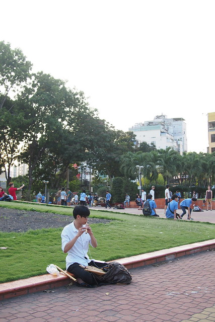 playing the flute in a park near Benh Than Market. Ho Chi Minh City (Saigon)