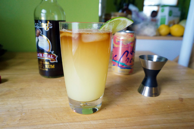 A glass of ginger beer sits on a wooden counterrop, with a darker layer floating at the top. In the background, a bottle of Black Seal rum is its own implicit explanation