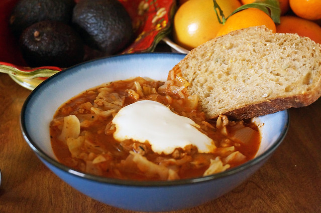 Stuffed cabbage soup, straight-on. A slice of multi-grain bread dips into the thick soup, while in the background a bright red bowl filled with avocados and a bowl of grapefruit and oranges mirror the rich red of the soup itself.