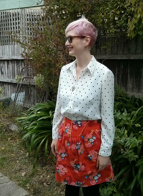 A woman wearing a polka dot button up shirt and floral skirt.
