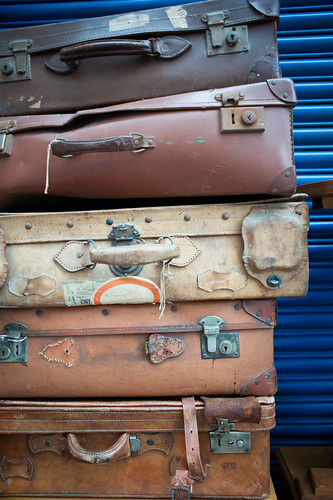 a stack of five antique suitcases