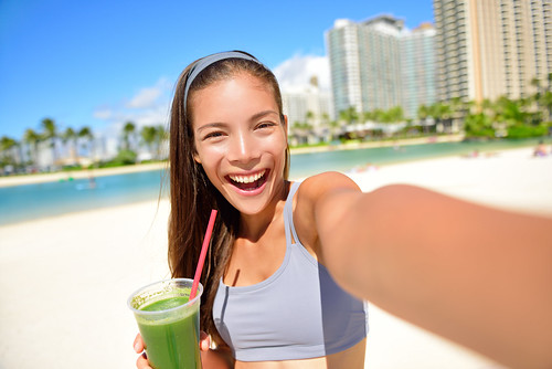 Fitness girl drinking green vegetable smoothie taking self portrait photograph with smart phone afte