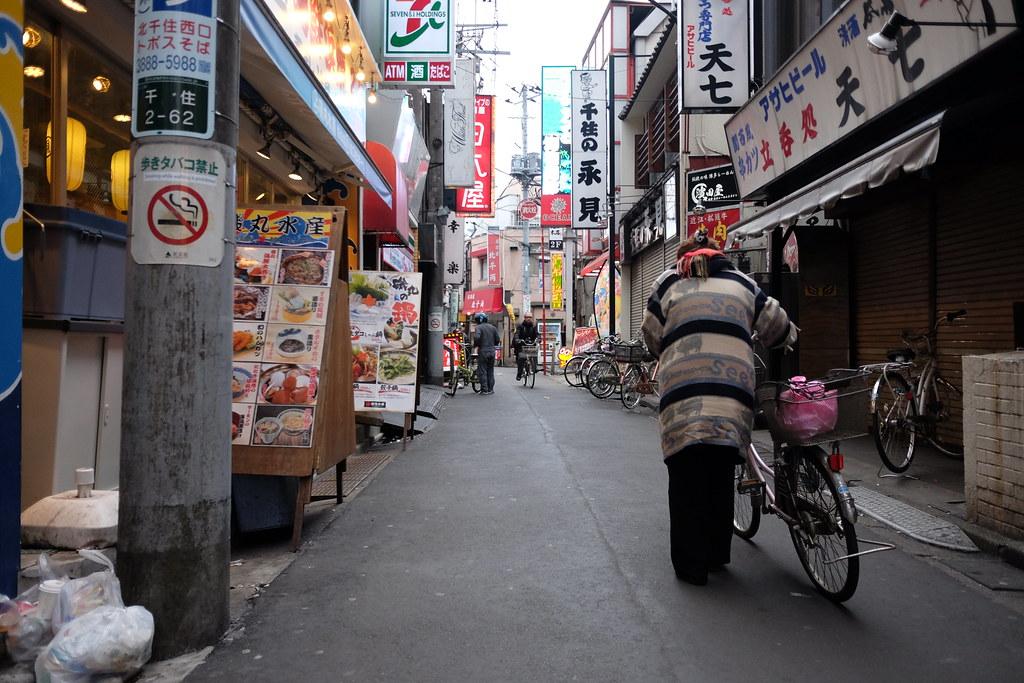北千住の飲み屋街を行く自転車のおばさん 2016/03/13 X7007410