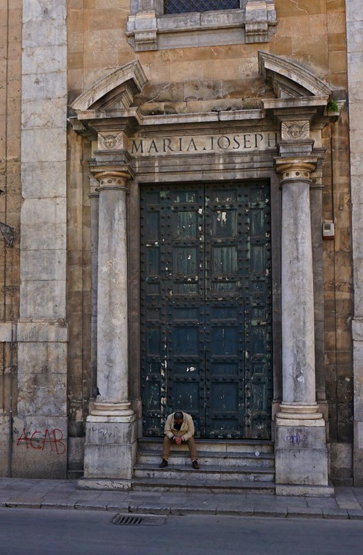 Man sitting on the church steps in the center of Palermo, Sicily