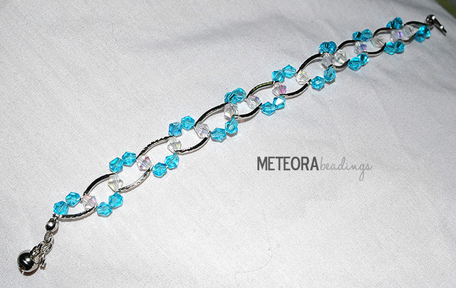 Bracelet - baby blue and clear beads, with silver spacers and bell