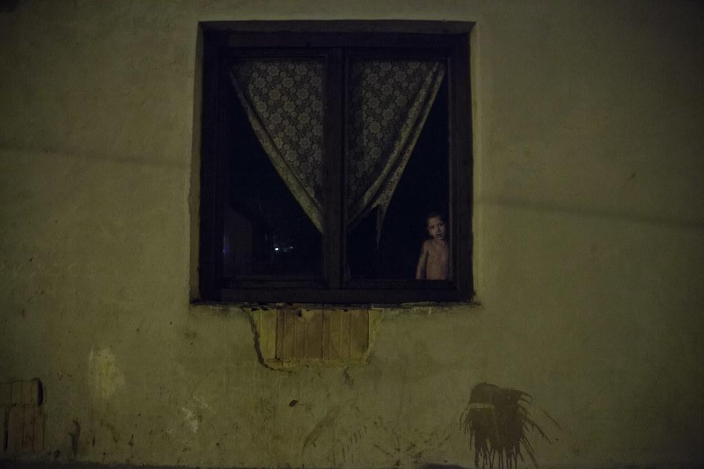 Éva egyik gyereke néz ki az utcára ablakukon. Éváéknál van egy zenedoboz, ami világít és egyben kisrádió is. Azt szokták bekapcsolni, és hallgatni. Most azonban le van merülve, fel kellene tölteni valamelyik szomszédnál. Náluk kilenc gyerek és két felnőtt lakik a kis szobában, a gyerekek közül csak négyen vannak otthon az édesanyjukkal. | Fotó: Magócsi Márton