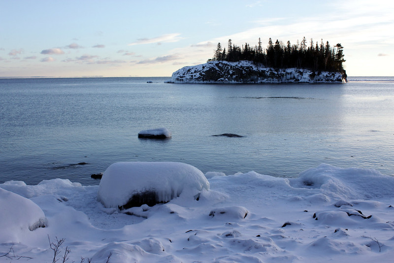 A small island with lots of pine trees, close to the snow-covered shore