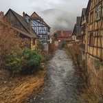 Half-timbered homes and spotty fog on the River Weiss. Taken from the 500 year-old Pont de Kaysersberg, France -- in the heart of the vineyards of Alsace.