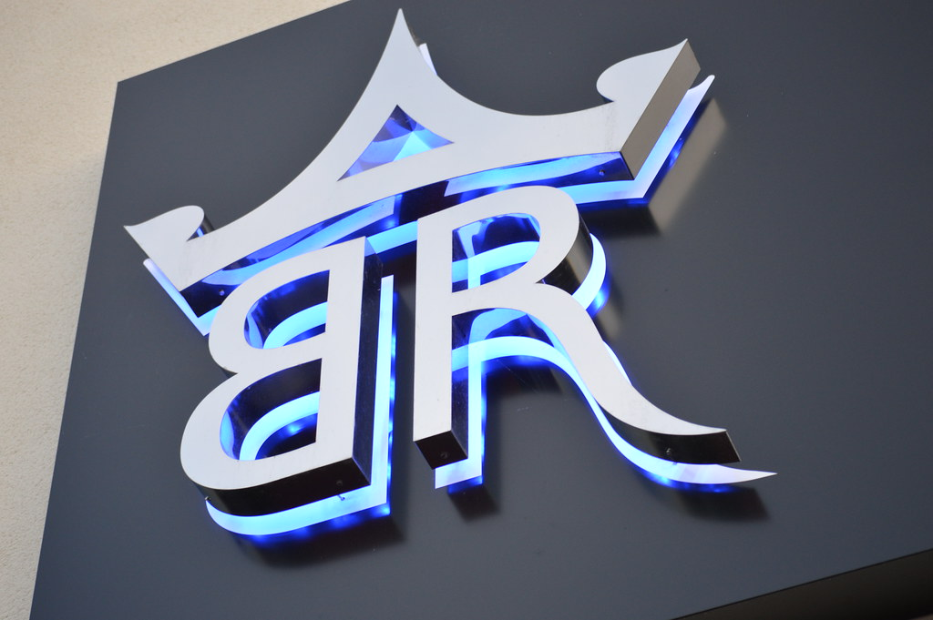 3D built up polished stainless steel letters/logo with blue LED halo illumination, mounted on an aluminium sign tray