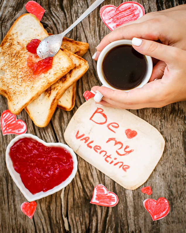 Toast with strawberry jam. Be My Valentine white message card with coffee in hands. Valentine's Day.