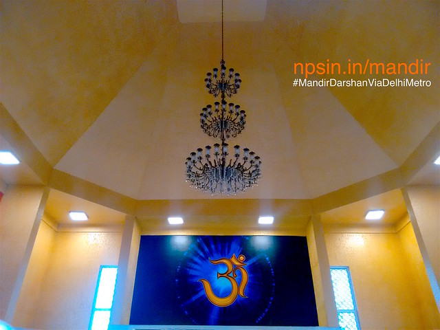 Beautiful lighting at the center, looks awesome. A jhumar with three stage of lighting effect with blue background of saffron Omkar frame.