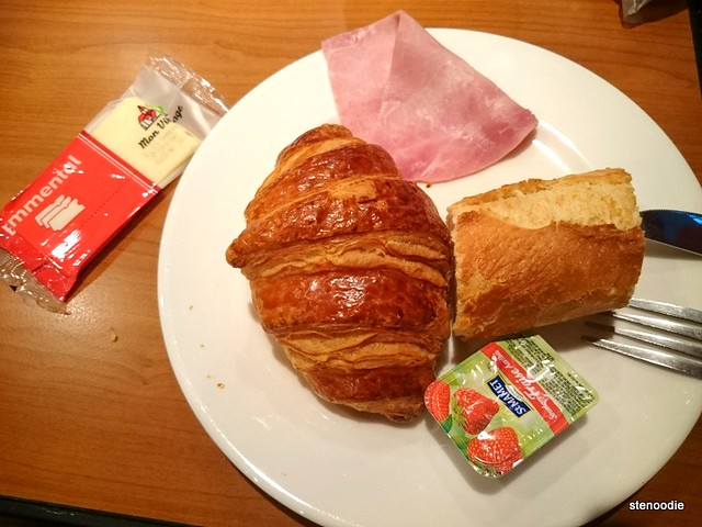 Plate of croissant, ham, cheese, bread, jam