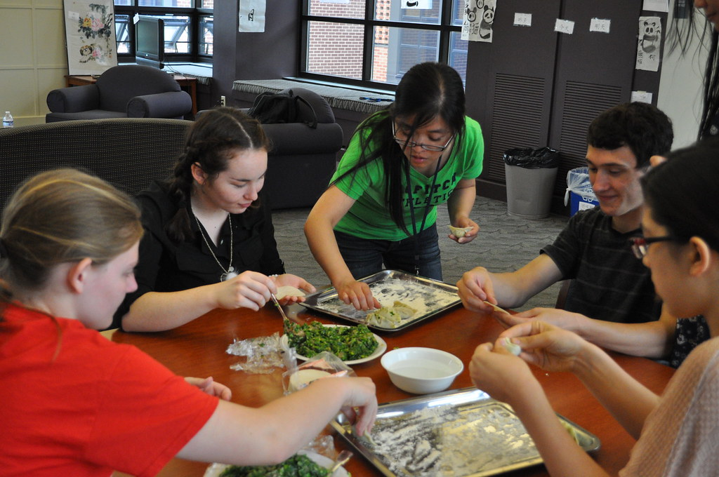 Instructor Hui Yu cooking with foreign language academy students.