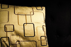 Patterned cushion on dark sofa dans actualitas fr 25926207362_43b3232393_m