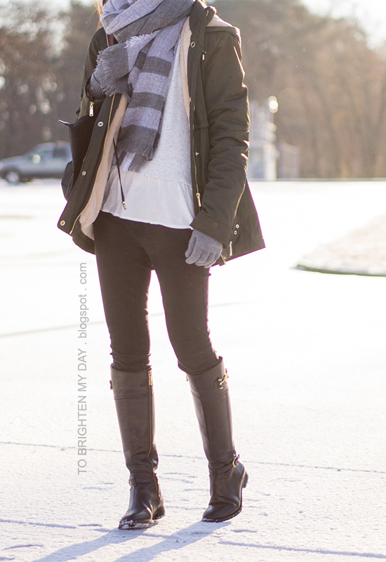 plaid oversized blanket scarf, military green parka, ruffled gray sweater, gray gloves, black riding boots
