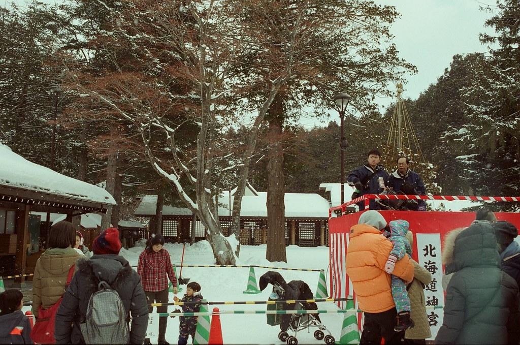 北海道神宮節分祭 Hokkaido, Japan / Fujifilm 500D 8592 / Nikon FM2 2016/02/04 北海道神宮節分祭,有對妖怪丟納豆的儀式,第一次搞懂原來丟納豆的祭典是怎樣的一回事,很新鮮。  那時候天空又飄起雪來,有點冷,站在那裡等很久,附近的居民慢慢聚集在舞台前,等到開始丟祈福的納豆時,大家都往前擠,有點恐怖!  不過真的還滿好玩的,這是這趟旅行第二次來到北海道神宮。  後來回到札幌車站附近的郵便局買明信片,看到電視在轉播各地的節分祭活動,稍微停下來看一下新聞,看看有沒有拍到我!  Nikon FM2 Nikon AI AF Nikkor 35mm F/2D Fujifilm 500D 8592 1114-0010 Photo by Toomore