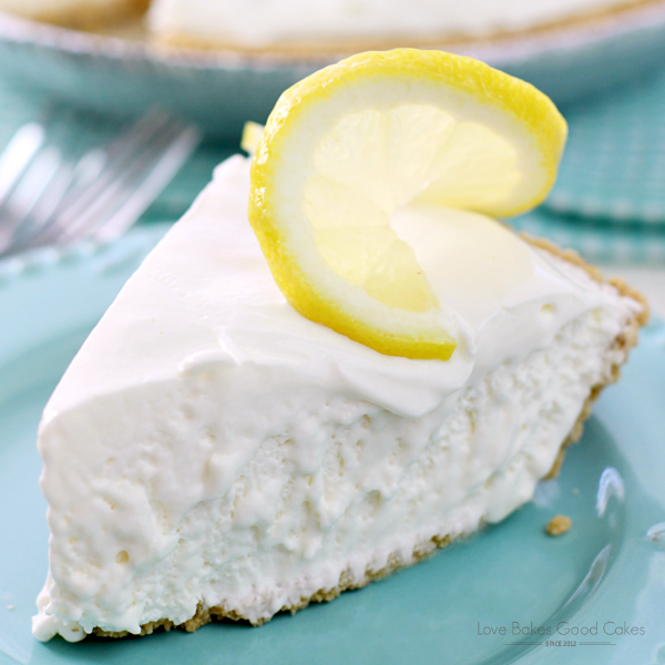 Frozen Lemonade Pie on a blue plate with a slice of lemon close up.
