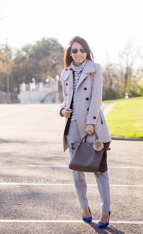 gray wool trench coat, gray turtleneck, black vest, gray trousers, blue suede pumps, gray tote with faux fur keychain